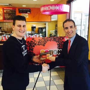 "Dunkin' Donuts Operations Director Lane Rodgers (right) presented Schalmont High School student-athlete Dante Gallucci with a $50 Dunkin' Donuts card during the launch of the ""Dunkin' Donors Make a Difference"" campaign at the Dunkin' Donuts at 1636 Central Avenue in Albany, NY on Monday, January 5. Gallucci, who plays football, basketball and track at Schalmont, has a rare form of cancer and is an American Red Cross blood recipient."