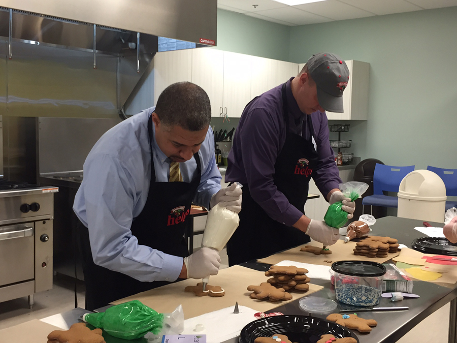 Capital District YMCA President and CEO Dave Brown (left) decorates holiday cookies alongside Hannaford Supermarkets Community Relations Specialist Brian Fabre (right) at the Hannaford store at 900 Central Avenue in Albany, NY on Tuesday, December 15. The cookies were distributed to local non-profit organizations, including the Regional Food Bank of Northeastern New York.