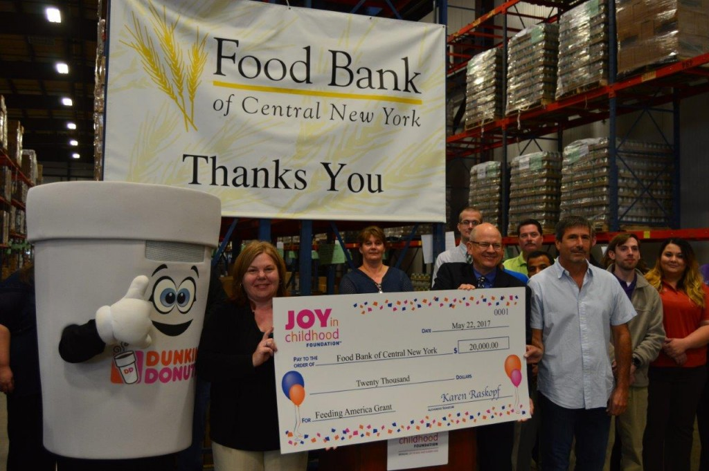 : Dunkin' Donuts Franchisee Tom Santurri and Dunkin' Donuts Field Marketing Manager Eric Stensland present a $20,000 check to Food Bank of Central New York Chief Operating Officer Karen Belcher while accompanied by Cuppie and Dunkin' Donuts associates.