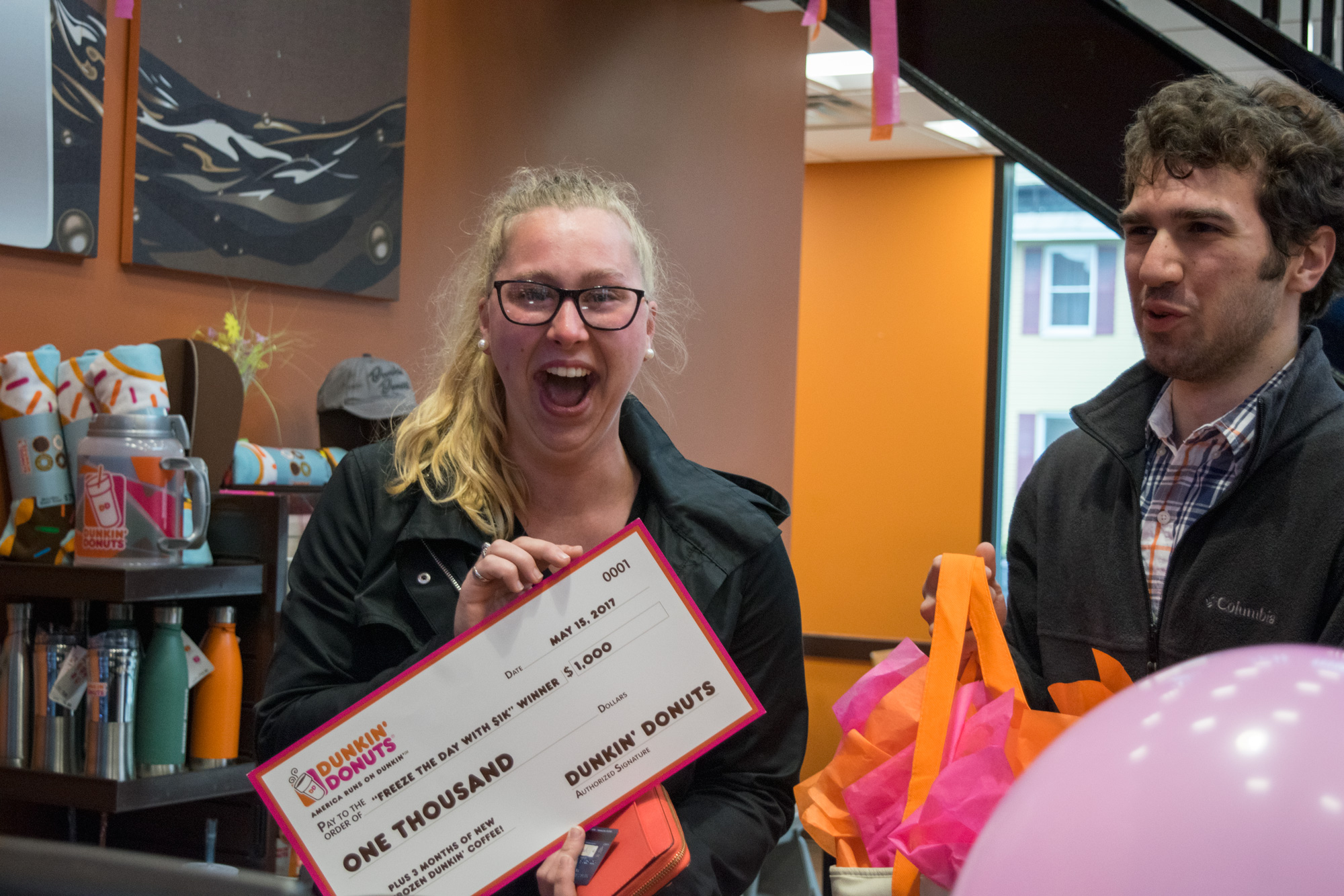 """Jennifer Leach, a senior at RPI, is surprised at the counter at the Dunkin' Donuts restaurant on Hoosick Street in Troy during their """"Freeze the Day with $1K"""" giveaway celebration on Monday, May 15. Jennifer is the recipient of $1,000, a three month supply of Frozen Dunkin' Coffee, and a special Freeze the Day themed prize pack. The """"Freeze the Day with $1k"""" program celebrates the new Frozen Dunkin' Coffee, a permanent menu item introduced nationally in May."""