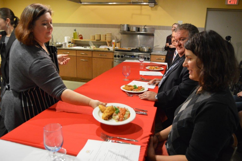 Jeanette Souther (left) presents her winning dish to the judging panel. Front right: Seven Days Food Writer Suzanne Podhaizer. Center right: WOKO On-Air Personality Rod Hill. Back right: ABC 22/FOX44 Anchor Bernie Lange.